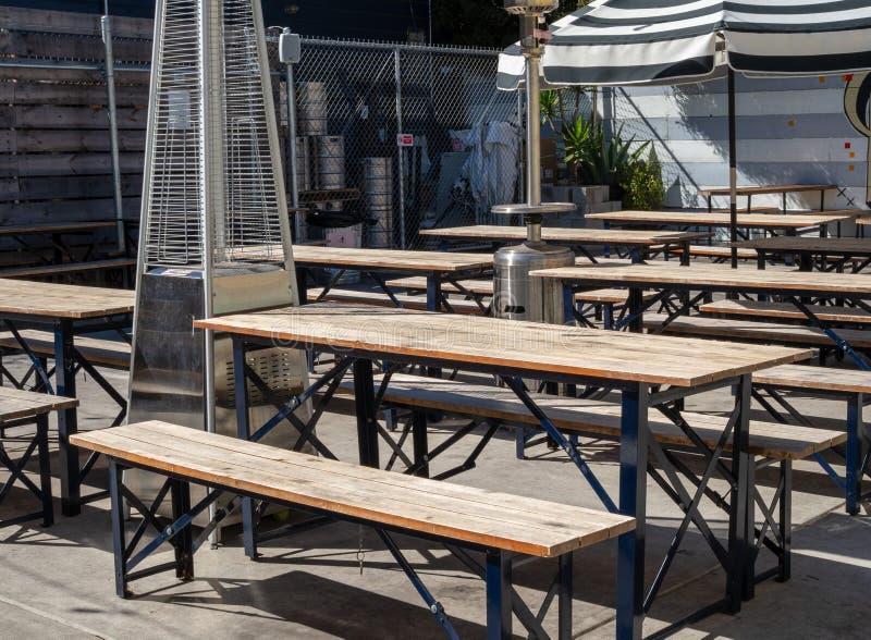 Mesas de picnic y paraguas al aire libre en un comedor al aire libre de la cervecería del restaurante durante día soleado foto de archivo