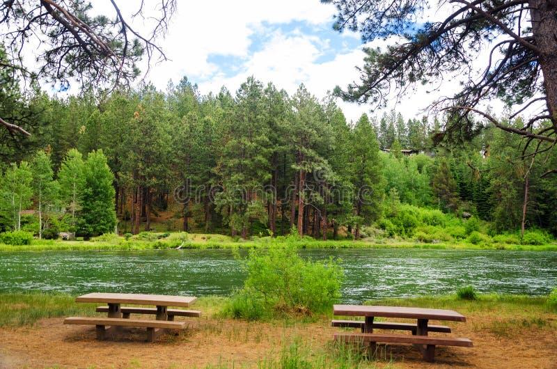 Mesas de picnic y río imagenes de archivo