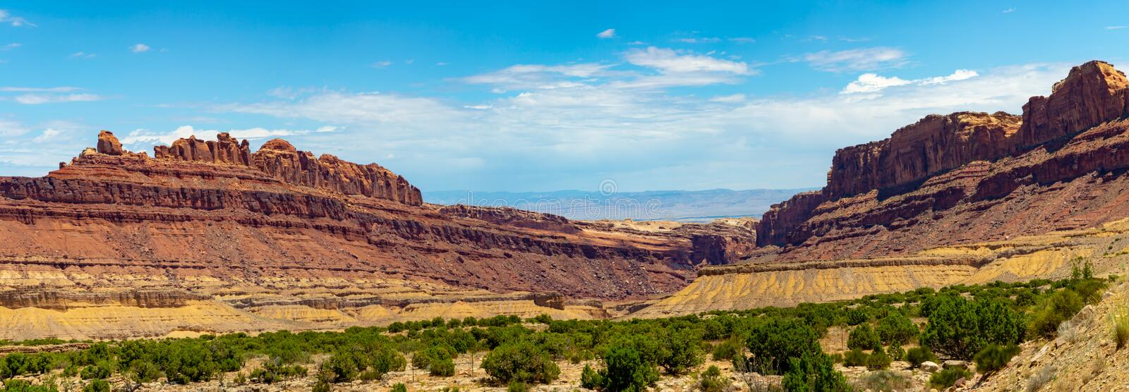 Mesas and Desert Canyons. A panorama rugged desert landscape in Utah shows different colored rocks, sands, and scrub plants stock photography