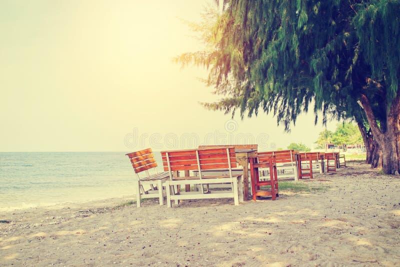 Mesas e cadeiras de madeira sob o pinheiro na praia fotos de stock royalty free