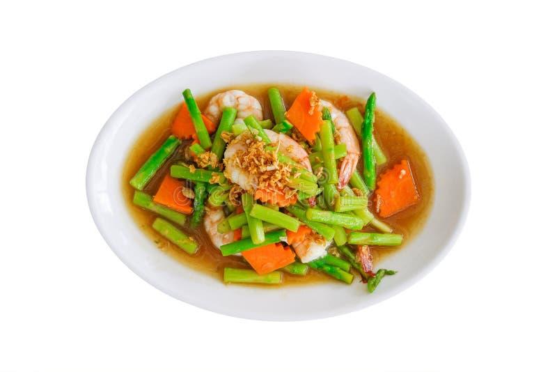 Mescoli l'asparago e la carota fritti con gamberetto sul piatto bianco isolato su bianco immagini stock