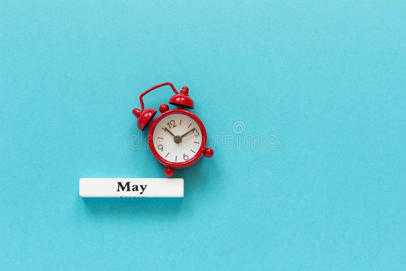 Mese di legno maggio della molla del calendario e sveglia rossa su fondo di carta blu Concetto ciao maggio o arrivederci vista su immagine stock libera da diritti