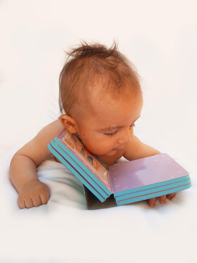 3 meses del bebé que juega con el libro imagenes de archivo