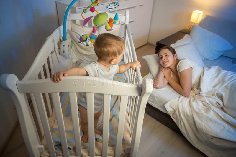 9 meses del bebé que se coloca en pesebre y que despierta su mothe cansado imágenes de archivo libres de regalías