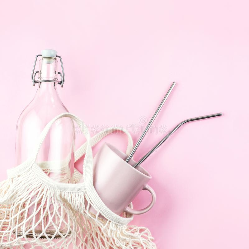 Mesh bag with reusable glass water bottle and cup on pink background. Sustainable lifestyle. Zero waste and no plastic concept stock images