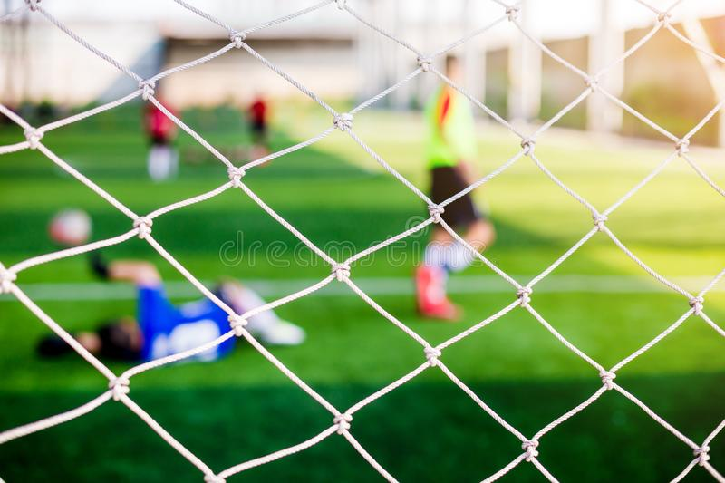 Mesh of goal with blurry of soccer goalkeeper and soccer players. Soccer ball training in academy stock photography