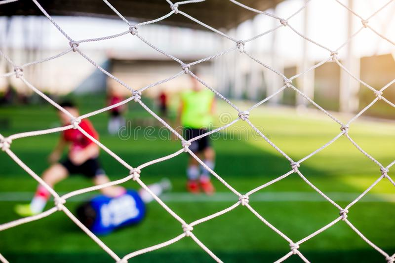 Mesh of goal with blurry of soccer goalkeeper and soccer players. Soccer ball training in academy royalty free stock photos