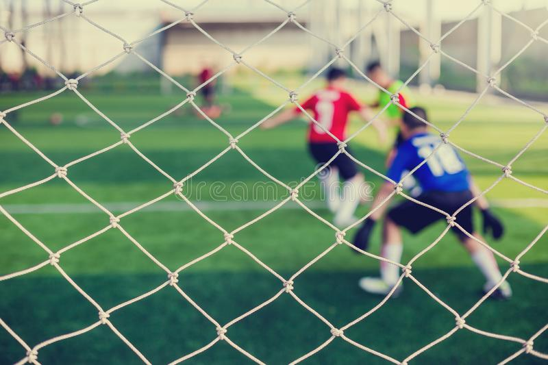 Mesh of goal with blurry of soccer goalkeeper and soccer players. Soccer ball training in academy stock photo