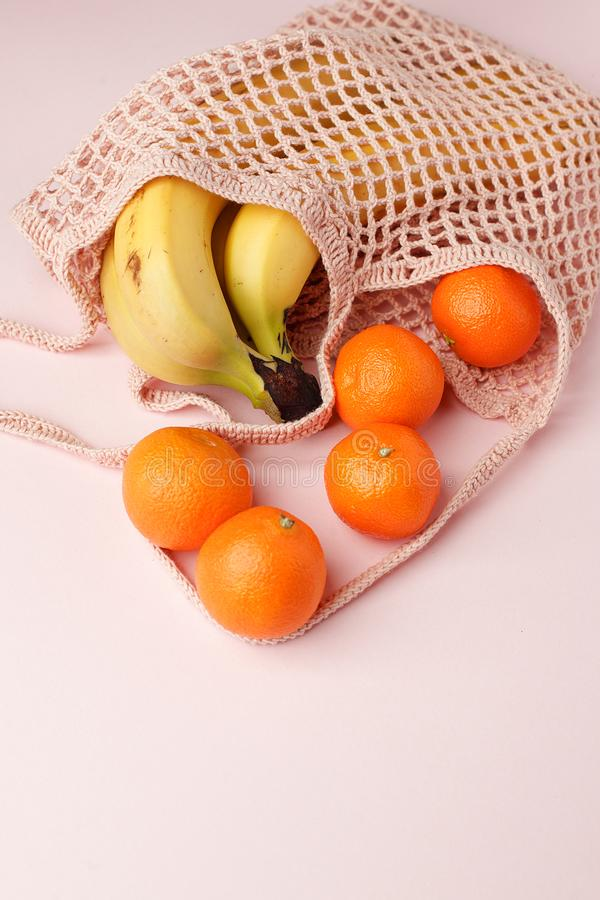 Mesh shopping bag with exotic fruits on pink canvas background. Summer time blogger organic food concept, minimal stock images