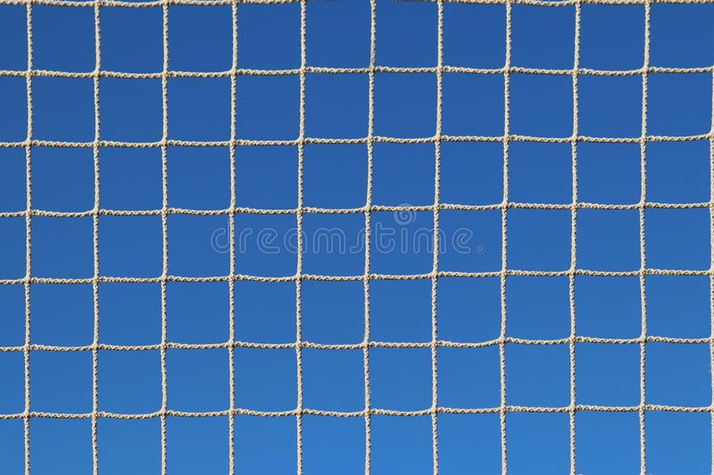 Mesh woven from a rope in the rays of clear sun against a blue sky. Transparent light burrowing. Dried out snap for catching fish. stock photos