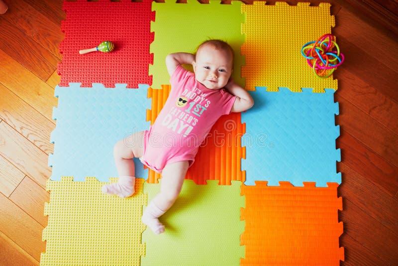 4 mesi della neonata che si trova sulla stuoia variopinta del gioco fotografie stock libere da diritti