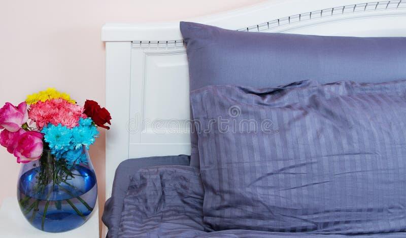 Mesita de noche con el florero de rosas de las flores y de aire fresco del dormitorio Cama con linos azules, manta, almohadas por fotografía de archivo