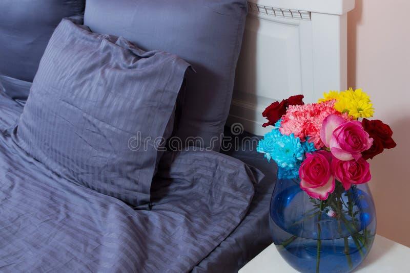 Mesita de noche con el florero de rosas de las flores y de aire fresco del dormitorio Cama con linos azules, manta, almohadas por foto de archivo