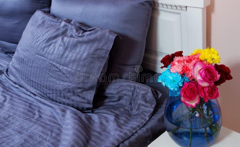 Mesita de noche con el florero de rosas de las flores y de aire fresco del dormitorio Cama con linos azules, manta, almohadas por fotos de archivo libres de regalías