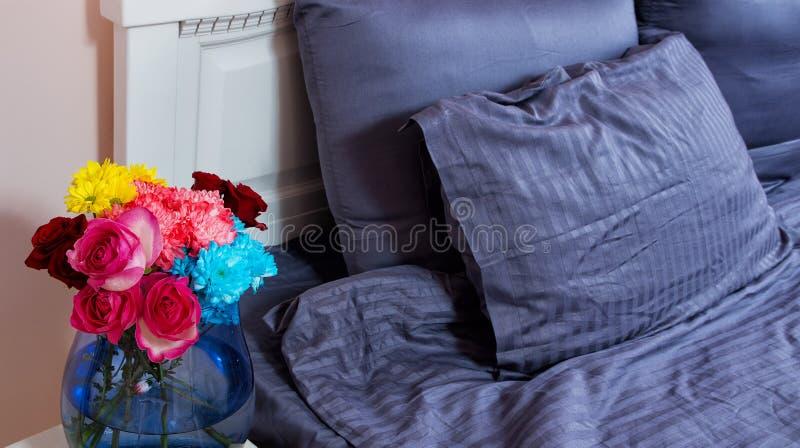 Mesita de noche con el florero de rosas de las flores y de aire fresco del dormitorio Cama con linos azules, manta, almohadas por imágenes de archivo libres de regalías
