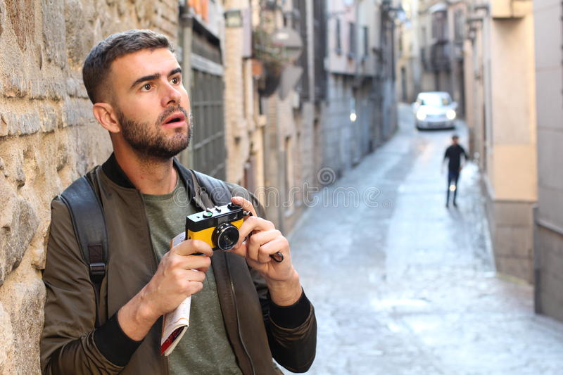 Mesmerized man holding a vintage camera during trip looking a something impressive.  stock photography