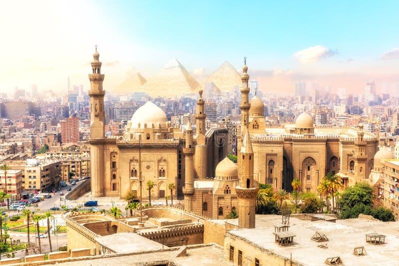A mesquita-Madrassa de Sultan Hassan e das pirâmides no fundo, vista bonita do Cairo, Egito imagem de stock royalty free