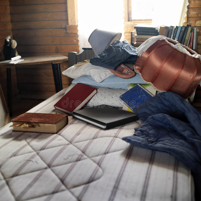Mess In A House. Books, lamp and garments scatterd on the unmade bed in a looking abandoned room, contra light indoor shot royalty free stock image