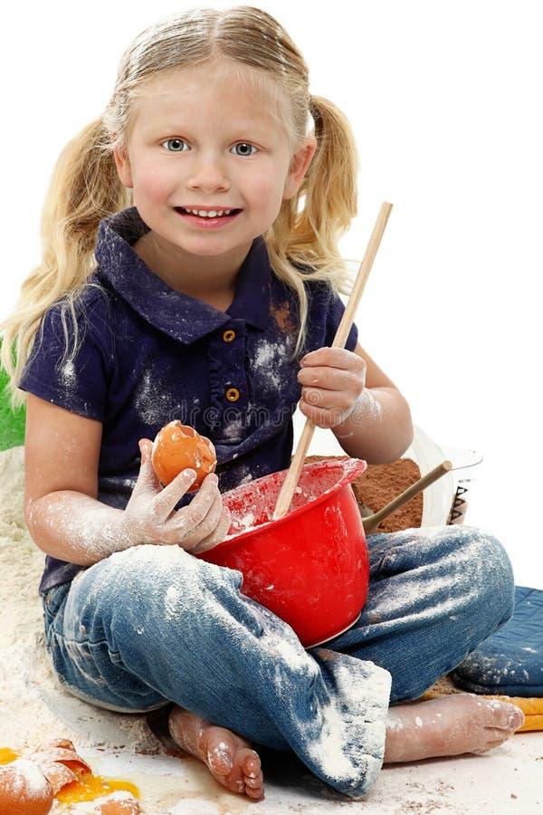 Mess pré-escolar bonito do cozimento da criança da menina fotografia de stock royalty free