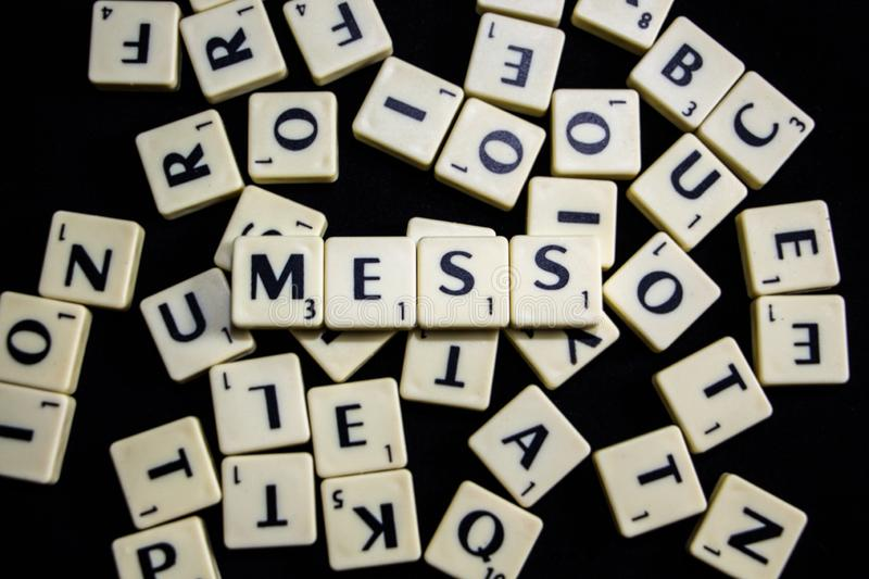 Mess word spelled with letter tiles in black background royalty free stock photo
