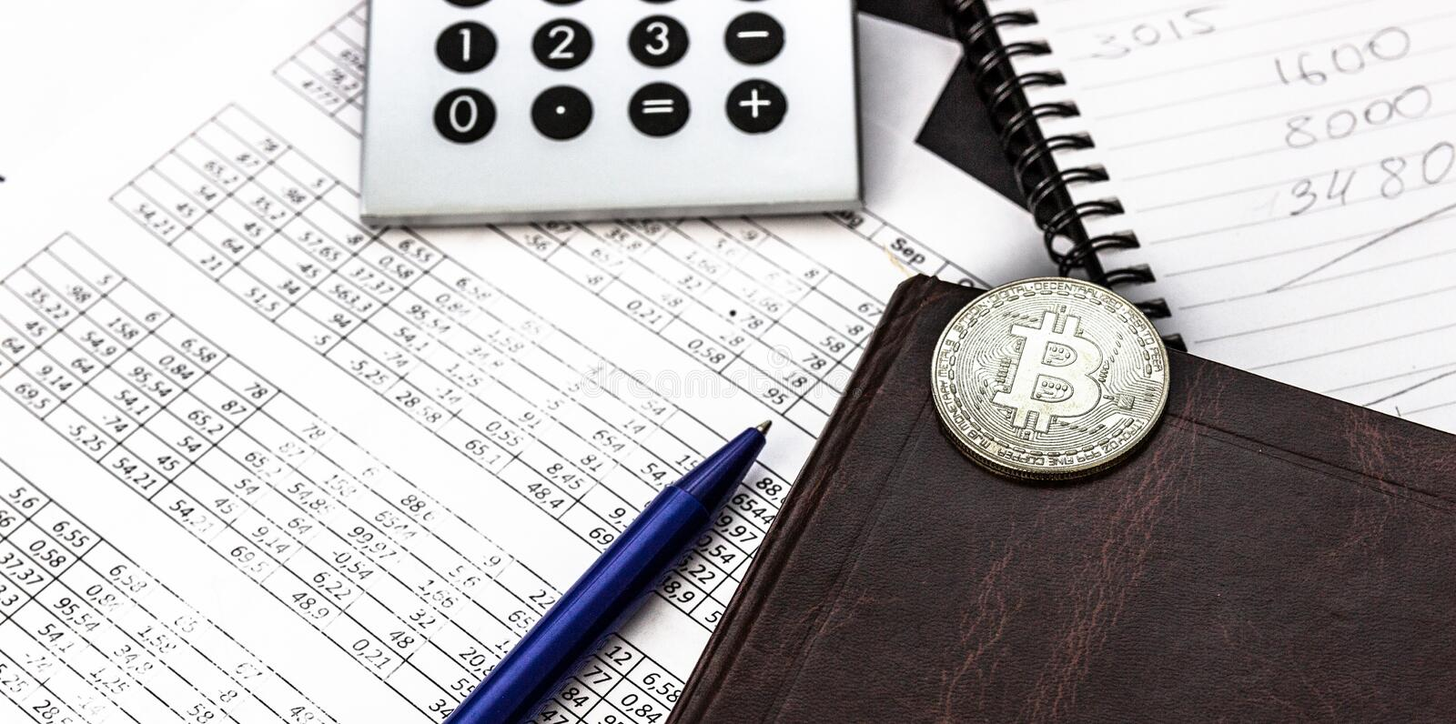 Mess on your desktop. Calculator, notebook, documents, Bitcoin, office supplies stock image