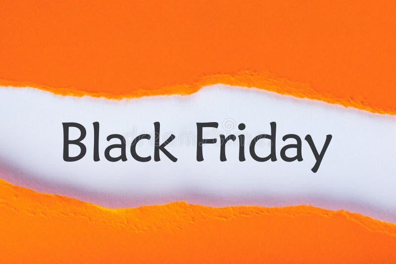Message apparaissant derrière le papier orange déchiré avec le texte de vente de Black Friday Temps d'achats Jour avec la plus gr image stock