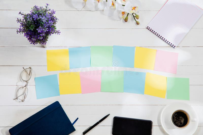 Message aux papiers de note colorés sur un fond de bureau photos stock