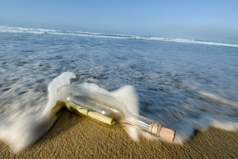 Message in a bottle. A bottle with a message inside of it washes ashore for a lucky person to discover stock images