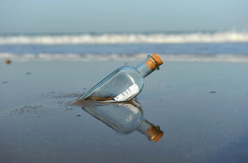 Message in a bottle on the beach stock images