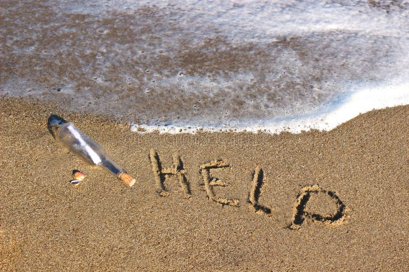 Message in a bottle at the beach and the word help. Scratched in the sand royalty free stock image