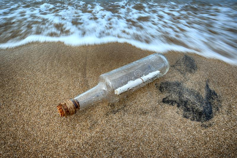 Message in a bottle in the sand of sea beach. Message in a bottle pushed by the waves of the sea on the beach with the cork attached by a rope stock illustration