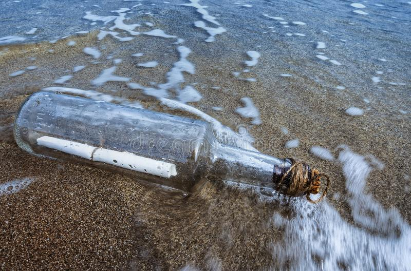Message in a bottle in the sand of sea shore. Message in a bottle pushed by the waves of the sea on the beach with the cork attached by a rope stock illustration
