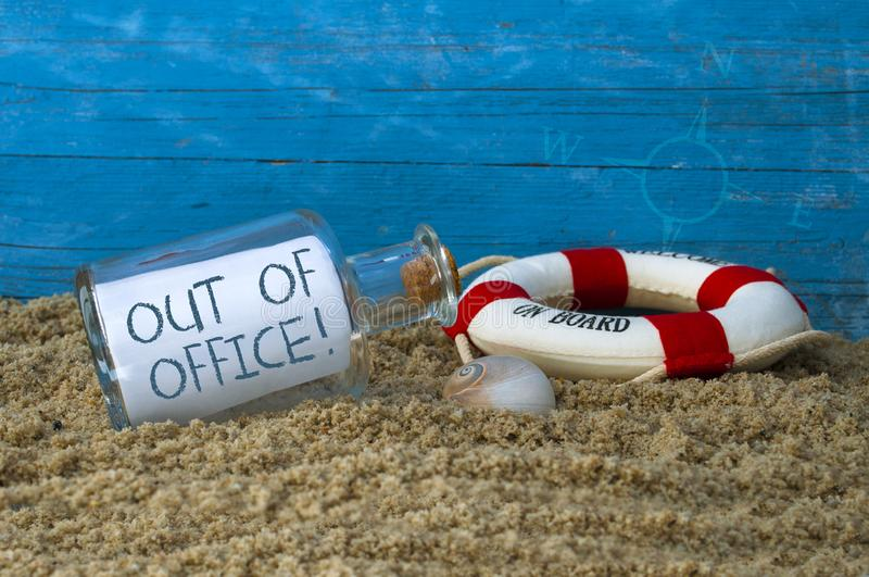 Message in a bottle in sand with message out of office in front of blue weathered wood. Message in a bottle in sand with message out of office royalty free stock image