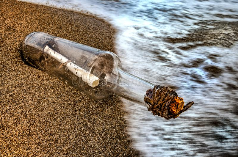 Message in a bottle in the sand of sea shore. Message in a bottle pushed by the waves of the sea on the beach with the cork attached by a rope vector illustration