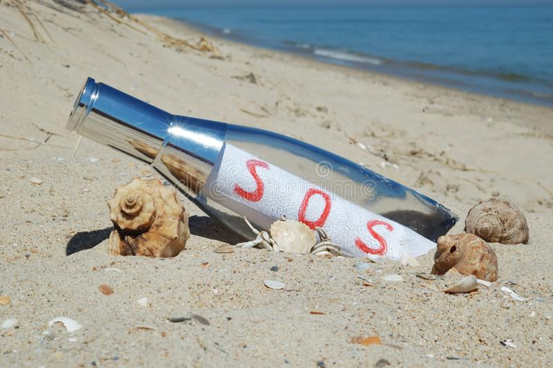 Message in a bottle with SOS signal royalty free stock photos