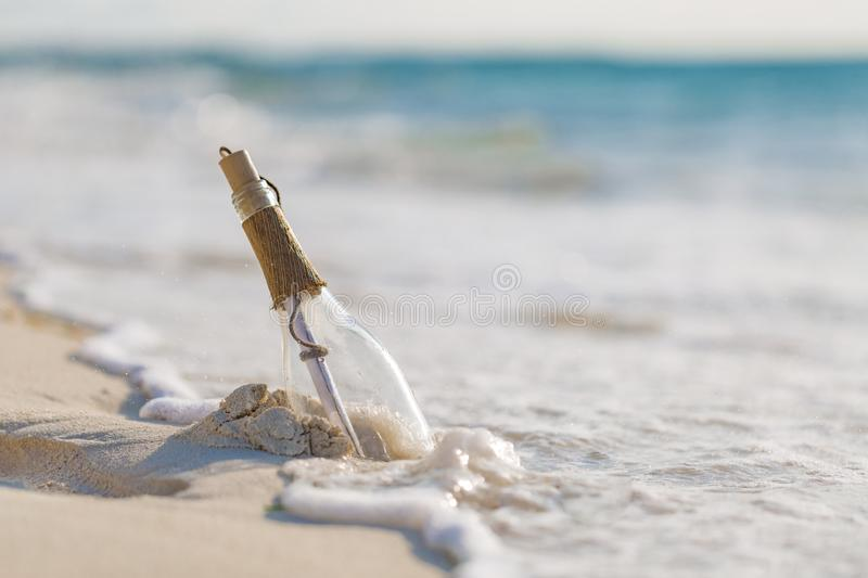 Message in a bottle on a tropical beach and blurred background. Inspire background design. Message in a bottle on a tropical beach and blurred background, soft royalty free stock photo