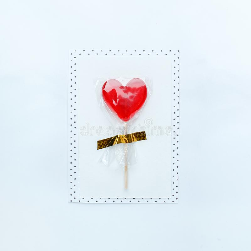 Message card with sugar red heart lollipop on white table. Valentines Day background, idea of diy postcard for 14 february, top royalty free stock photo