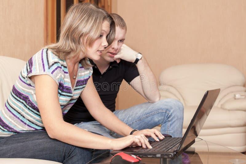 Message caucasien inquiété d'impression d'homme et de femme et regarder l'écran de l'ordinateur portable, émotion pendant jouer d image stock