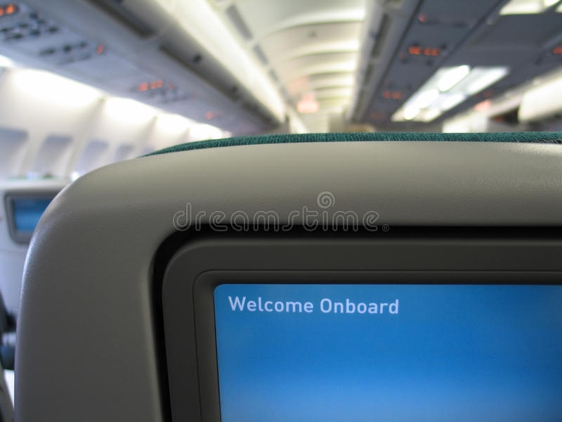 Message d'accueil sur l'écran dans l'intérieur d'avion image stock