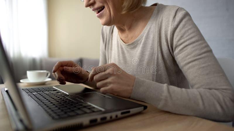 Message de dactylographie âgé heureux de dame sur l'ordinateur portable, communiquant sur le site Web de datation images stock