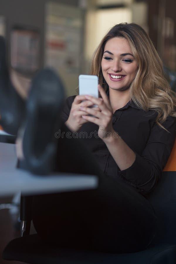 Message de dactylographie d'affaires Jeune femme sûre dans la tenue de détente futée tenant le téléphone intelligent et le regard photo libre de droits