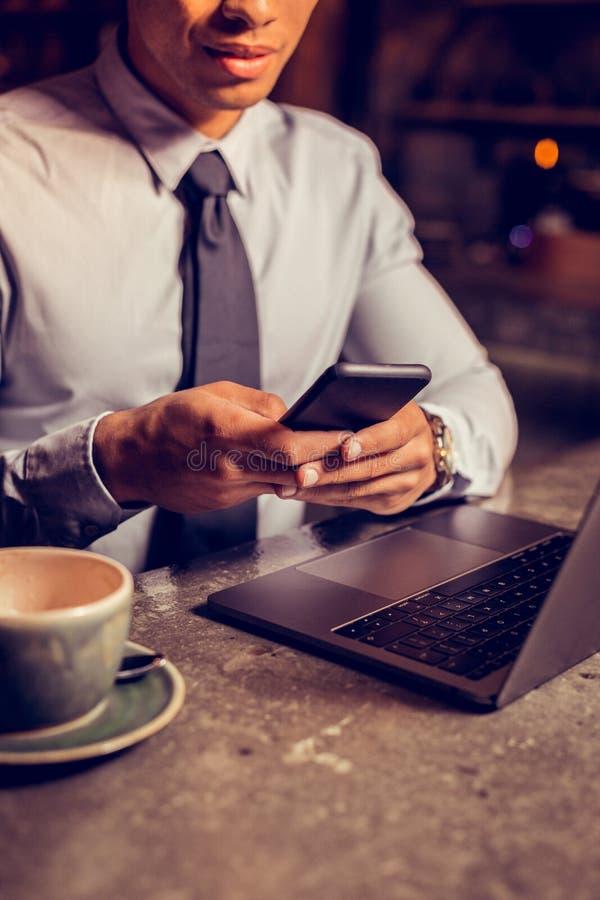 Message de dactylographie d'homme d'affaires au téléphone après avoir bu du café photo libre de droits