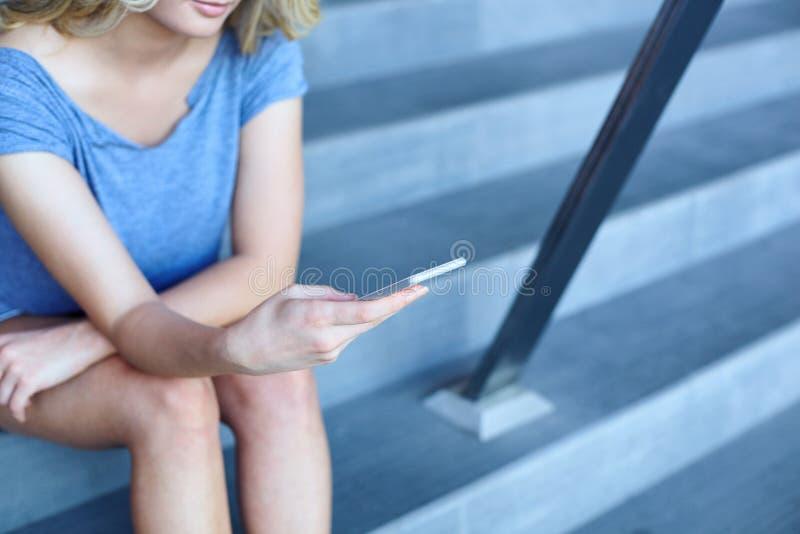 Message de dactylographie de fille au téléphone portable et se reposer sur des escaliers images stock
