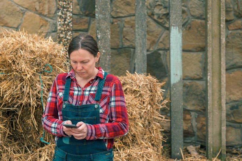 Message de dactylographie de sms d'agriculteur f?minin au t?l?phone portable photographie stock libre de droits