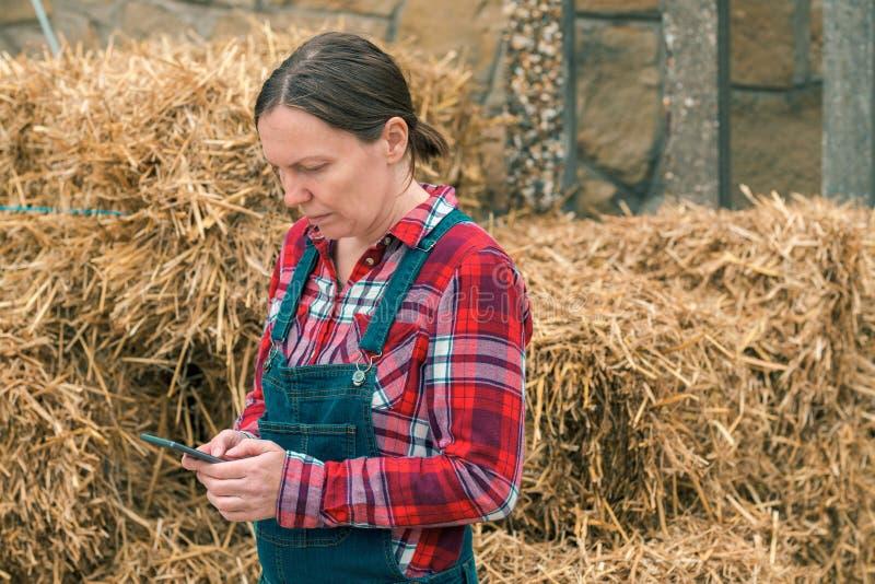 Message de dactylographie de sms d'agriculteur f?minin au t?l?phone portable images libres de droits