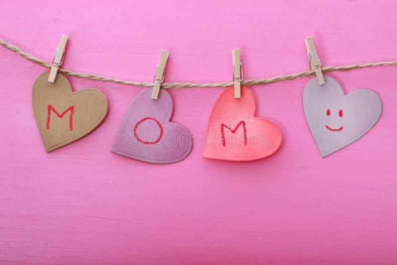 Message de jour de mères sur les coeurs de papier images stock