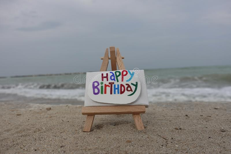 Message de joyeux anniversaire découpé et peint sur une pierre au-dessus d'un chevalet avec le fond de plage image libre de droits