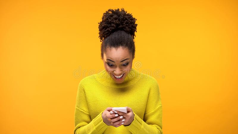 Message de lecture femelle africain heureux de smartphone, excitation de bonnes nouvelles, causerie photographie stock libre de droits