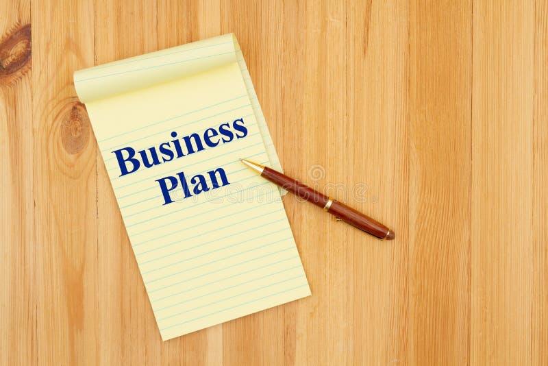 Message de plan d'entreprise sur un bloc-notes et un stylo sur un bureau en bois photographie stock libre de droits