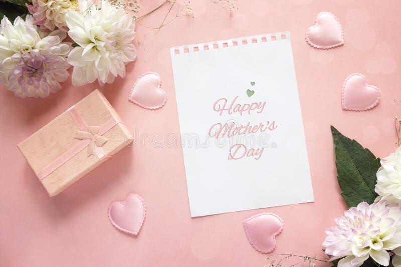 Message de salutation de jour de mères avec les dahlias et le boîte-cadeau sur un rose photographie stock